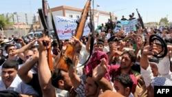 Thanh niên Iraq nâng vũ khí và hô khẩu hiệu ủng hộ lời kêu gọi của giáo sĩ Ayatollah Ali al-Sistani, ở thành phố thánh địa Najaf, 14/6/2014.