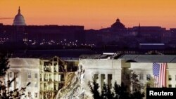 The damaged area of the Pentagon building, Islamic extremists flew a plane into it September 11, is seen in the early morning at sunrise with the U.S. Capitol Building in the background, September 16, 2001.
