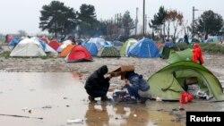 Những người di cư cố gắng chuẩn bị một bữa ăn dưới cơn mưa rào tại một trại tạm thời ở biên giới Hy Lạp-Macedonian, gần làng Idomeni, Hy Lạp, ngày 09/3/2016.