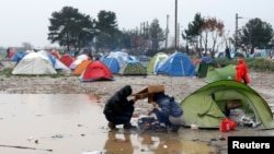 在希腊与马其顿边界的一个临时搭建的难民营里,移民试图在雨中做饭。(2016年3月9日)