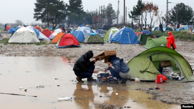 Migrants try to prepare a meal during a rainfall at a makeshift camp on the Greek-Macedonian border, near the village of Idomeni, Greece, March 9, 2016.
