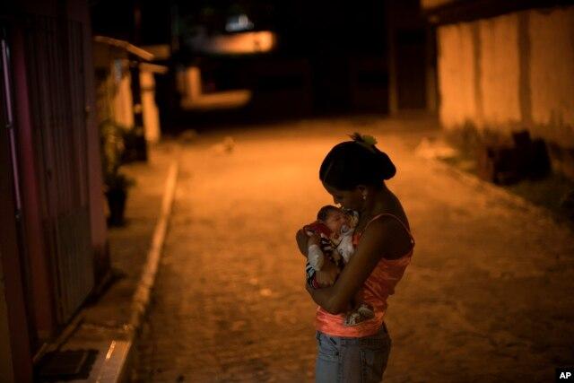 Cô Daniele Ferreira dos Santos ôm cậu con trai Juan Pedro, bị tật nhỏ đầu, bên ngoài ngôi nhà của cô ở Brazil. Santos chưa bao giờ bị nhiễm virut Zika nhưng cô cho rằng virut này đã gây nên tật nhỏ đầu của con cô.