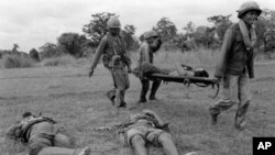 Three Khmer Republican soldiers carry a wounded comrade past two dead soldiers north of Phnom Penh, in 1975. The Khmer communists kept Republican troops busy around the capital while the communists fought for total control of the Mekong River in the south