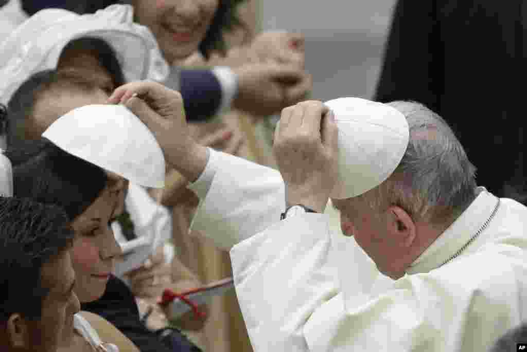 تبادل کلاه بین پاپ فرانسیس رهبر کاتولیک های جهان با یکی از پیروان مسیحی در واتیکان