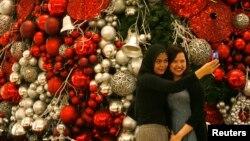 Dua orang pengunjung mal di Jakarta berfoto di depan pohon Natal (23/12). (Foto: Dok)