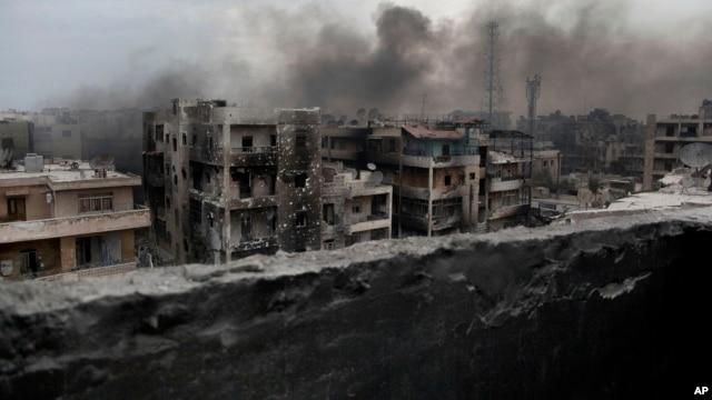 FILE - Smoke rises over Saif Al Dawla district, in Aleppo, Syria.