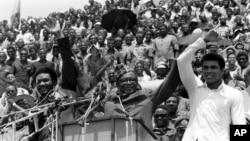 Le président du Zaïre (devenu RDC), Mobutu Sese Seko, au centre, soulève la main de Mohamed Ali, à droite, et de George Foreman, à gauche, sous les acclamations des dizaines de zaïrois réunis au stade du 20 Mai (rebaptisé Tata Raphaël) quelques jours avant le combat du championnat mondial de boxe entre les deux boxeurs poids-lourds, à Kinshasa, Zaïre (RDC), 17 septembre 1974. (AP Photo)