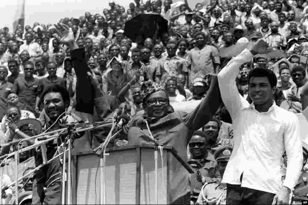 Le président du Zaïre Mobutu Sese Seko, lève la main de Muhammad Ali quand il le présente avec son challenger George Foreman avant le combat du championnat WBA/WBC au cours d'un meeting populaire au stade du 20 Mai où les deux boxeurs disputerontle titre quelques jours plus tard. (AP Photo).