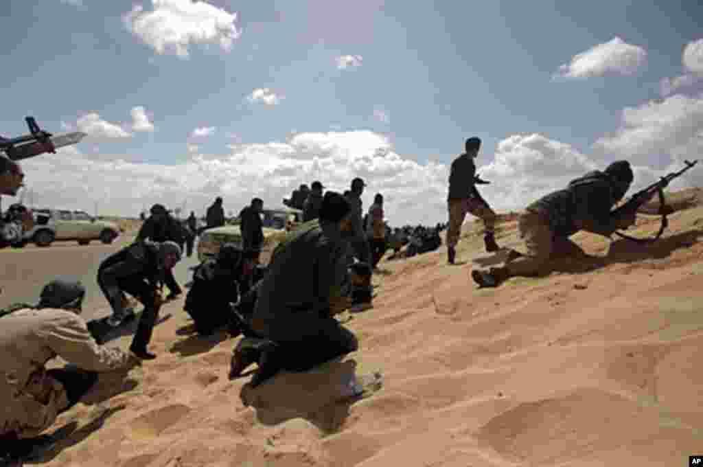 Rebeldes líbios em Ajdabiya, procuram abrigo durante uma ofensiva fracassada das tropas de Kadhafi