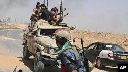 Rebelles libyens revenant d'un combat à 100 kms de Tripoli