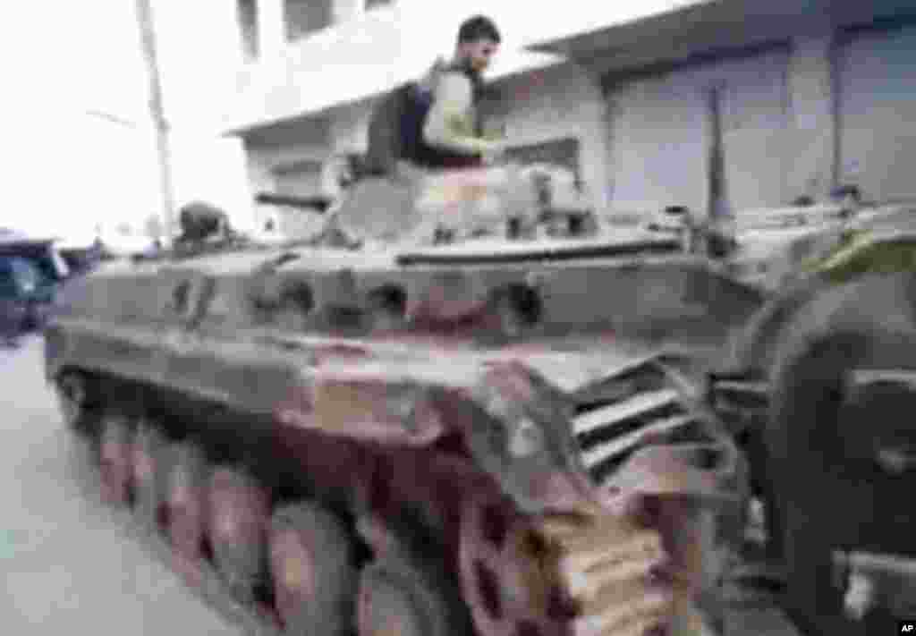 This image from amateur video and released by Shaam News Network purports to show a Syrian rebel atop of a Syrian military tank in Khan Sheikhoun, Syria, March 13, 2012. (AP/Shaam)