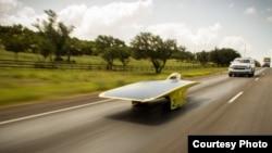 University of Michigan's 2014 solar car, Quantum, speeds down the highway in the American Solar Challenge. (Darren Cheng)