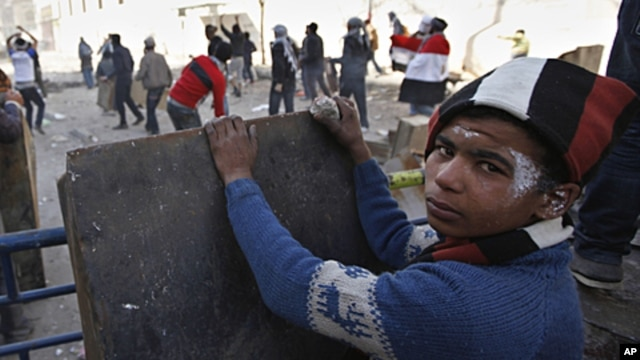 An Egyptian boy takes cover while others throw stones during clashes with the security forces near the interior Ministry in downtown Cairo, Egypt, February 3, 2012.