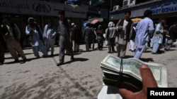 FILE - A money changer holds a stack of U.S. dollars at Kabul's largest money market April 23, 2014. The U.S. has reportedly spent $113 billion rebuilding Afghanistan, more than it spent rebuilding Europe after World War II, adjusted for inflation.
