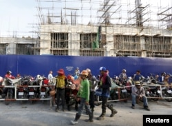 FILE - Laborers rest in front of a construction site of the HongKong Land in Phnom Penh, Cambodia, Oct. 19, 2015. High-rise apartments are springing up across Cambodia's capital, part of a property boom led by expat demand, while developers are also betting on the middle class.