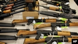 FILE - A cache of seized weapons is displayed in Phoenix, Jan. 25, 2011.