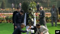 President Barack Obama, left, participates in a tree planting ceremony at the Raj Ghat Mahatma Gandhi Memorial, New Delhi, India, Jan. 25, 2015.
