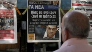 A man reads the front pages of various newspaper hanging at a kiosk in Athens, June 29, 2015.