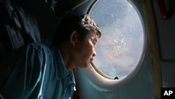 Officer Lang Van Ngan of the Vietnam Air Force looks out the window onboard a flying AN-26 Soviet made aircraft during a search operation for the missing Malaysia Airlines flight MH370 plane over the southern sea between Vietnam and Malaysia, March 14, 20