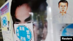 "Poster pencarian buron Katsuya Takahashi diberi stiker bertuliskan ""tertangkap"" di sebuah kantor polisi di Tokyo (15/6). Takahashi, mantan anggota Aum Shin Rikyo, pelaku serangan gas sarin kereta api bawah tanah Jepang tertangkap di sebuah cafe buku komi"