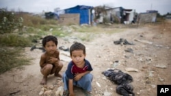 Two young Cambodian boys play near their slum home on the outskirts of Phnom Penh.