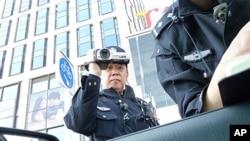 هێزێـکی پـۆلیس چینی سهیری پاسپـۆرت و ناسـنامهی پهیامنێری دهنگی ئهمهریکا له بهیژین دهکهن، یهکشهممه 24 ی چواری 2011