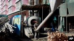 Trabajadores toman parte de una obra de un edificio residencial en Xiahe, en la provincia de Gansu, en China.