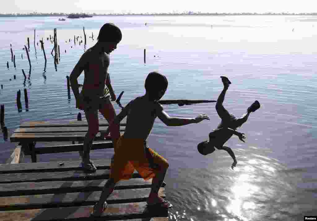 Boys jump from a cut-off foot bridge, which was damaged by Typhoon Haiyan, in Tacloban City in central Philippines. Almost 25,000 people still live in tents, shelters and bunkhouses in the hardest hit regions. The Philippines are preparing to commemorate