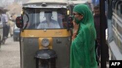 Pakistanka prelazi ulicu u Karačiju pokrivajući lice zbog lošeg kvaliteta vazduha, koji prema izveštaju SZO udiše devet od svakih deset stanovnika sveta (Foto: AFP/Rizwan Tabassum)