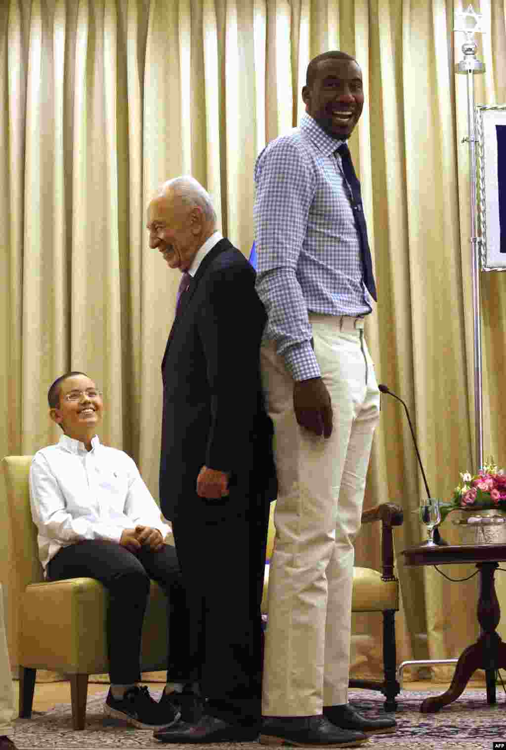 Israeli President Shimon Peres stands back to back with NBA basketball player Amar'e Stoudemire of the New York Knicks at the presidential residency in Jerusalem.