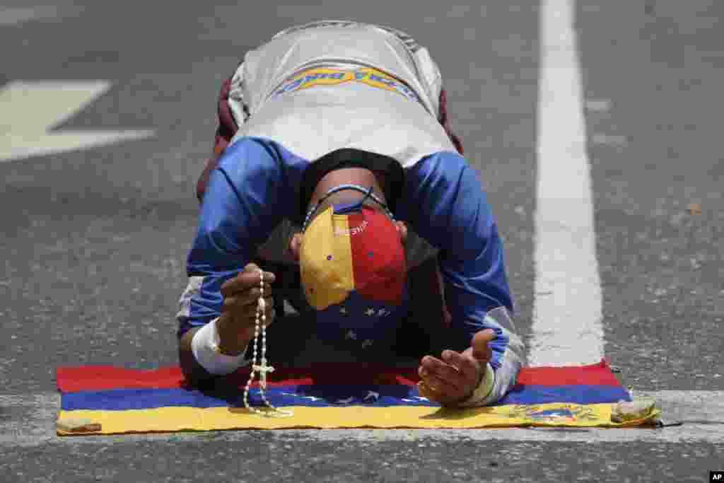 បាតុករម្នាក់មានកាន់ផ្កាក្នងដៃ កំពុងបួងសួងនៅលើទង់ជាតិវេណេស៊ុយអេឡា នៅមុនពេលពួកគេចាប់ផ្តើមបន្តបាតុកម្មប្រឆាំងនឹងរដ្ឋាភិបាលរបស់លោកប្រធានាធិបតី Nicolas Maduro នៅទីក្រុងការ៉ាកាស ប្រទេសវេណេស៊ុយអេឡា។