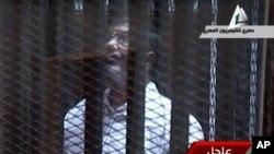 Mantan Presiden Mesir Mohamed Morsi disidangkan atas tuduhan pembobolan penjara, di Kairo hari Selasa (28/1).