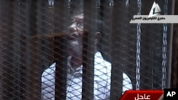 Video menunjukkan mantan Presiden Morsi berteriak-teriak ke arah hakim dari kurungan yang kedap suara (28/1).