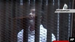 Ảnh trích từ truyền hình Ai Cập cho thấy ông Mohammed Morsi, tổng thống bị lật đổ đứng trong phòng bọc kính và kim loại trong tòa án ở Cairo, Ai Cập, 28/1/14