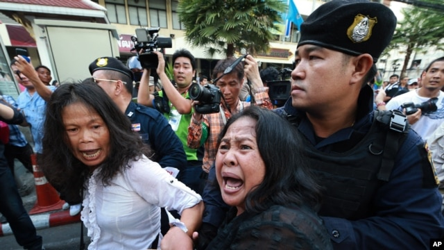 A woman tries to help as an anti-coup protester is detained by a Thai police officer during a street protest in Bangkok, Thailand, on May 24, 2014.