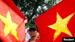 Bui Thanh Hieu, a dissident blogger, holds Vietnamese national flags while marching during an anti-China demonstration near the Chinese embassy in Hanoi July 3, 2011.