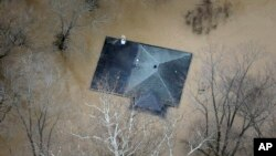 In this aerial photo, floodwater reaches the rooftop of a house in Valley Park, Mo., near St. Louis, Dec. 31, 2015.