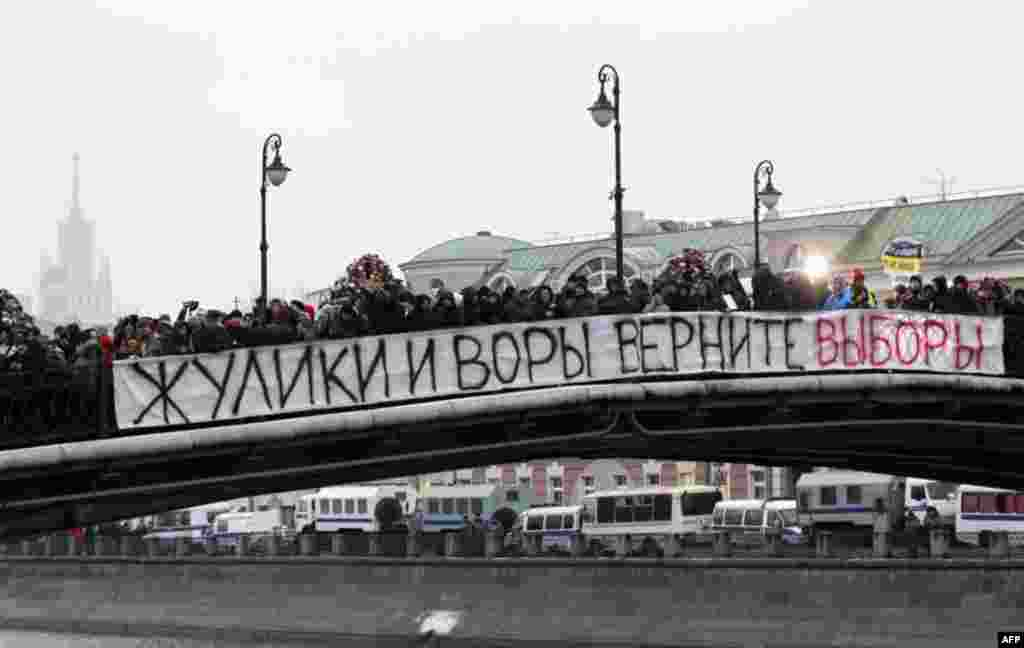 People stand on the bridge as they attend a mass rally to protest against alleged vote rigging in Russia's parliamentary elections in Moscow, Russia, Saturday, Dec. 10, 2011. Many thousands of Russians angered by allegedly fraudulent parliamentary electio
