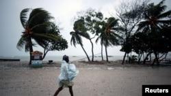 Mwanamke ajikinga kutokana na kibunga Mathew kwenye ufukwe wa Les Cayes Haiti mapema Jumatatu.