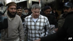 U.S. consulate employee, identified as Raymond Davis, is escorted by police and officials out of court after facing a judge in Lahore, January 28, 2011
