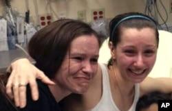 逃出被囚禁的阿曼达•北里(右)2013年5月6日在俄亥俄州的克利夫兰医院和她的妹妹贝思(侧)见面。