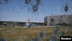 Pos perbatasan di Ukraina terlihat dari lubang-lubang peluru sebuah jendela truk di luar kota Luhansk (3/6).