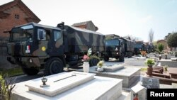 A convoy of Italian Army trucks arrives from Bergamo carrying bodies of coronavirus victims to the cemetery of Ferrara, Italy, where they will be cremated, Saturday, March 21, 2020.
