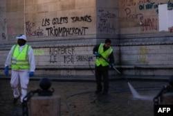 """Radnici čiste oko Trijumfalne kapije dan nakon demonstracija žutih prsluka zbog podizanja cena goriva i životnih troškova, 2. decembra 2018. u Parizu. Grafit na spomeniku znači """"žuti prsluci će trijumfovati"""""""