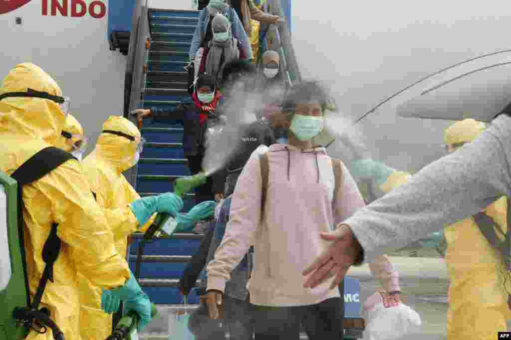 This handout photo released by the Indonesian Embassy shows officials in full protective gear disinfecting Indonesian students as they disembark upon the arrival at Hang Nadim international airport in Batam, following their evacuation from the Chinese city of Wuhan due to the coronavirus outbreak.