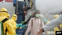 This handout photo taken and released by the Indonesian Embassy on February 2, 2020, shows officials in full protective gear disinfecting Indonesian students as they disembark upon the arrival at Hang Nadim international airport in Batam.