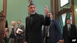 Afghan President Hamid Karzai greets journalists as he leaves a press conference at the presidential palace in Kabul, Afghanistan on Jan. 25, 2014.