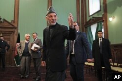 Afghan President Hamid Karzai greets journalists as he leaves a press conference in Kabul, Jan. 25, 2014.
