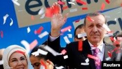 FILE - Turkey's President Tayyip Erdogan, accompanied by his wife Emine Erdogan, attends the opening ceremony of an imam-hatip school in Ankara, Nov. 18, 2014.
