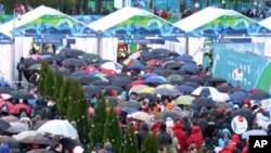 Visitors line up to enter the Winter Games venues on opening day. Umbrellas were plentiful, snow was not